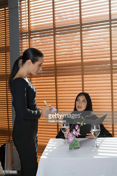 Waitress takes order from Arab woman at restaurant table. United Arab Emirates