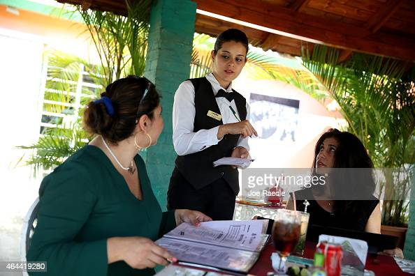 A waitress takes the orders from customers at the restaurant 'El Balcon' a restaurant run out of a private home on February 25 2015 in Havana Cuba US...