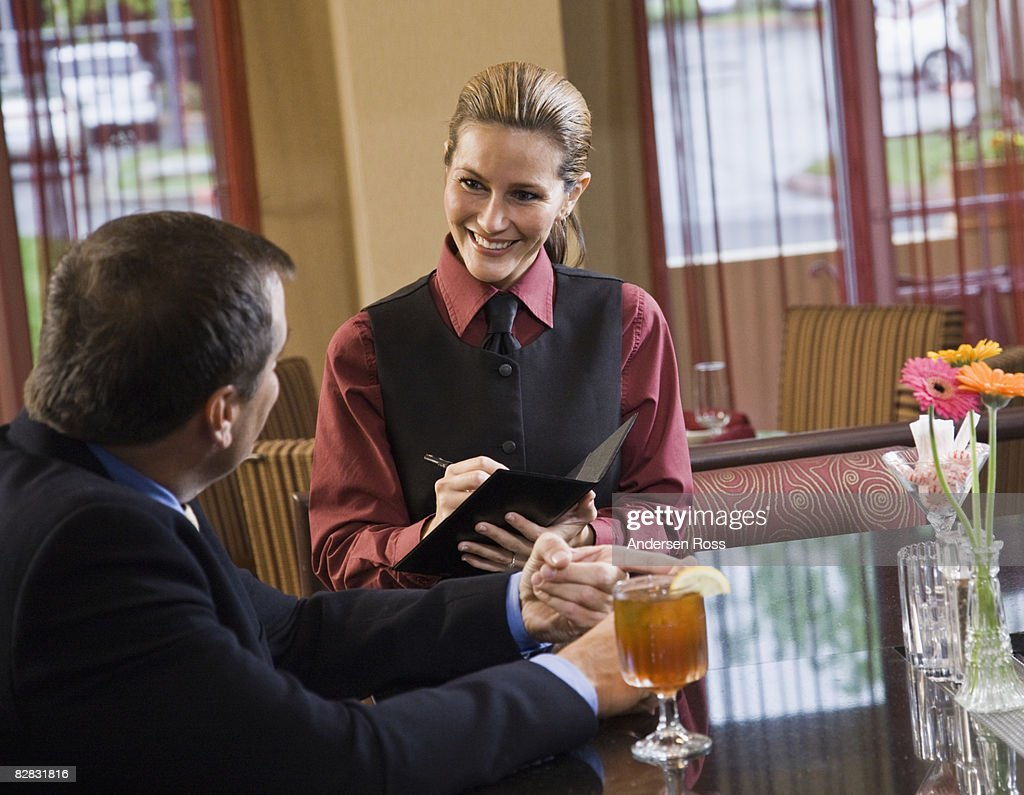 Waitress taking a male patron's order : Stock Photo