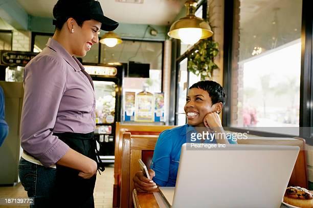 Waitress taking businesswoman's order in restaurant