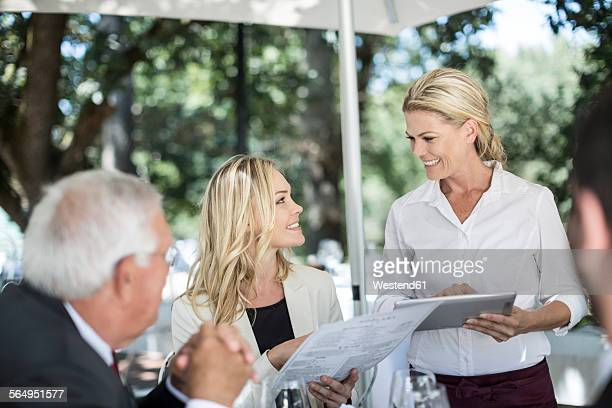 Waitress taking clients lunch orders at table using a digital tablet