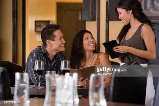 Waitress taking couple's order in restaurant