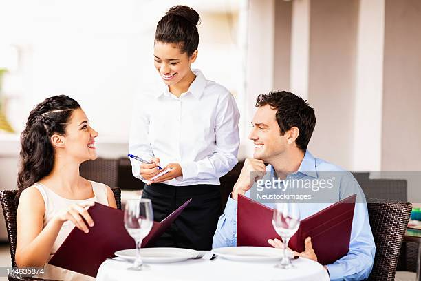 Waitress Taking Order From Couple At Restaurant