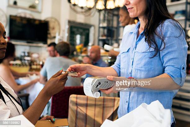 Waitress Taking Payment With Credit Card Terminal