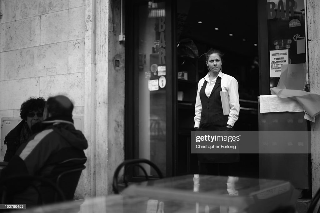 A waitress waits for customers at her cafe on March 15, 2013 in Rome, Italy. Daily life continues around the vatican as romans prepare for the inauguration mass of Pope Francis, the first ever Latin American Pontiff.