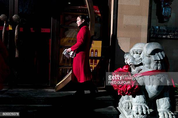 A waitress waits for customers outside a restaurant in Beijing on January 17 2016 China recorded its lowest growth in a quarter of a century in 2015...