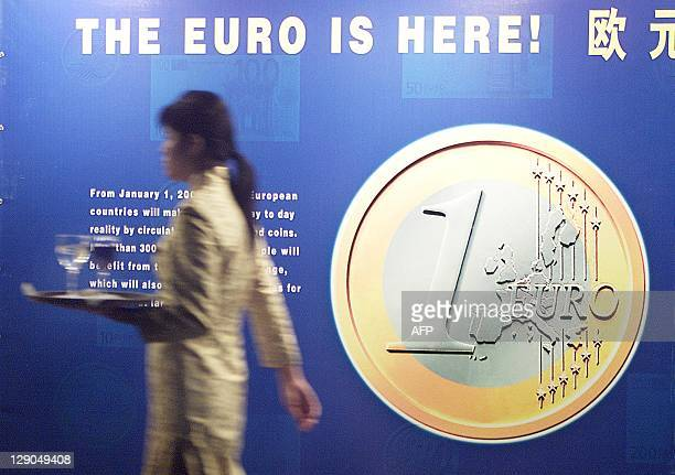 A waitress walks past a sign at the opening ceremony of 'The Euro is Here' exhibition 20 November 2001 in Beijing Held in the China Numismatic Museum...