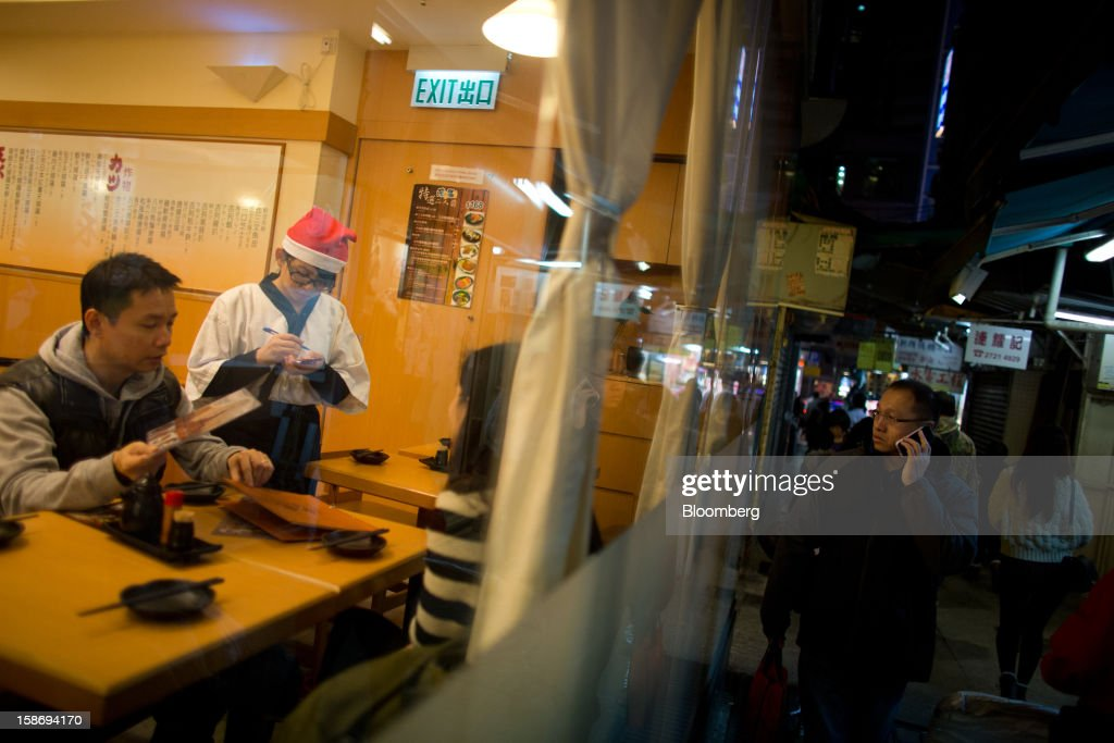 A waitress wearing a Santa Claus hat takes an order from customers inside a Japanese restaurant in the Tsim Sha Tsui area of Hong Kong, China, on Saturday, Dec. 22, 2012. Hong Kong's economy is set for its weakest annual expansion since the global financial crisis as the European sovereign debt crisis damps global trade. Photographer: Lam Yik Fei/Bloomberg via Getty Images