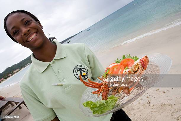 Waitress with lobster lunch, Coconut Beach French Creole Restaurant, Grand Anse Beach.