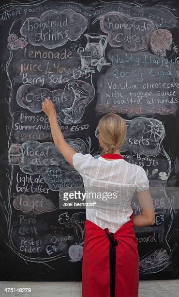 Waitress writing on blackboard menu in cafe