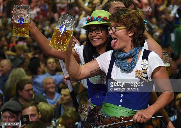 Waitresses celebrate the end of the 183th Oktoberfest on a table in a festival tent of the beer festival in Munich southern Germany on the evening of...