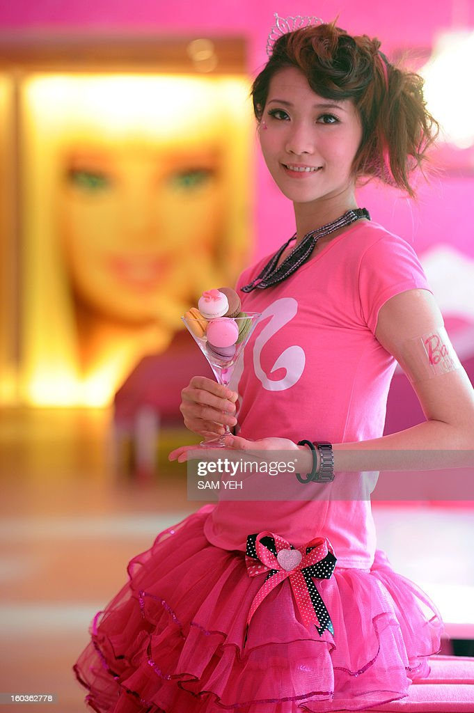 A waitresses poses as she displays a cup of macarons during the opening ceremony of a Barbie-themed restaurant in Taipei on January 30, 2013. With hot pink sofas, high heels-shaped tables and chairs decorated with tutus, the first Barbie-themed restaurant opened in Taiwan on January 30 catering to fans of the iconic doll. AFP PHOTO / Sam Yeh