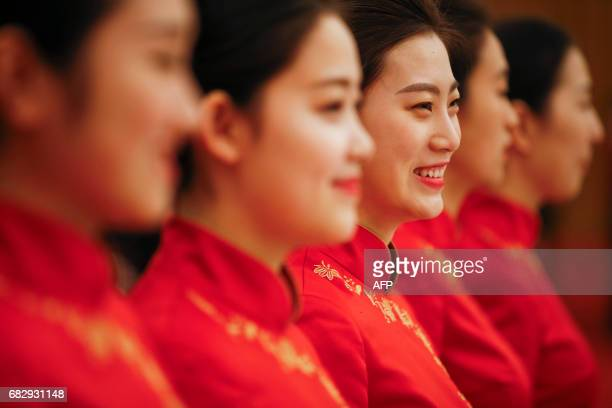 Waitresses wait by tables ahead of a welcoming banquet at the Great Hall of the People during the first day of the Belt and Road Forum in Beijing on...