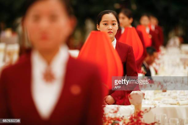 Waitresses wait by tables served for welcoming banquet at the Great Hall of the People during the first day of the Belt and Road Forum in Beijing on...