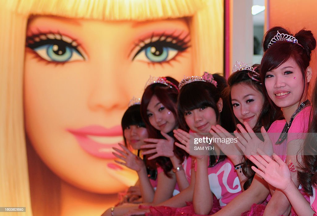 Waitresses wave in front of a Barbie poster during the opening ceremony of a Barbie-themed restaurant in Taipei on January 30, 2013. With hot pink sofas, high heels-shaped tables and chairs decorated with tutus, the first Barbie-themed restaurant opened in Taiwan on January 30 catering to fans of the iconic doll. AFP PHOTO / Sam Yeh