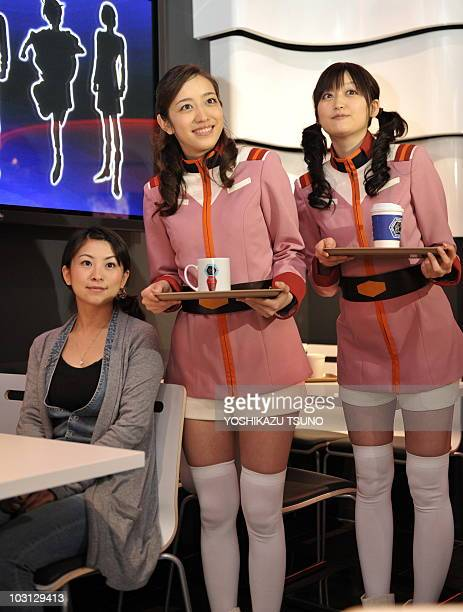 Waitresses wearing costumes from Japan's robot animation 'Gundam' pose for photo at a press preview of the 'Gandum Cafe' the animation characters...
