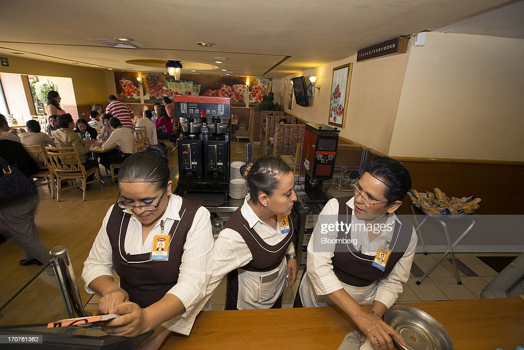 Waitresses work at a Vips restaurant in the El Toreo neighborhood of Mexico City, Mexico, on Monday, June 17, 2013. Wal-Mart de Mexico SAB de CV, known as Walmex, is considering offers to sell its restaurant division, which includes the Vips, El Porton, Ragazzi and La Finca brands. Photographer: Susana Gonzalez/Bloomberg via Getty Images