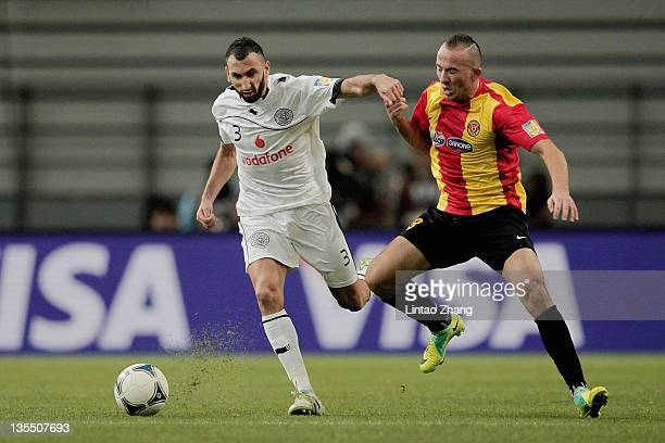 Wajdi Bouazzi of Esperance Sportive De Tunis and Nadir Belhadj of AlSadd Sports Club challenge for the ball during the FIFA Club World Cup Quarter...