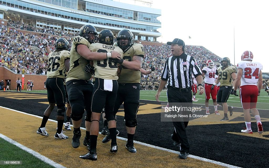 Wake Forest's Cory Helms, left, and Tyler Hayworth celebrate with Jared Crump (88) after he made a 3-yard touchdown reception during the second half against North Carolina State at BB&T Field in Winston-Salem, North Carolina, on Saturday, October 5, 2013. Wake Forest won, 28-13.