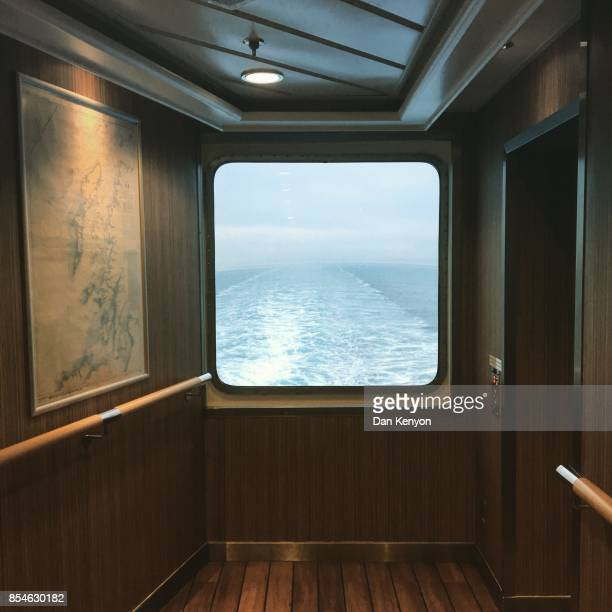 Wake of ship seen through window with map on wall