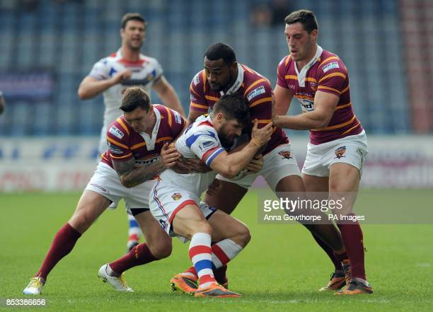 Wakefield Wildcats' Jarrod Sammut is tackled by Huddersfield Giants' Danny Brough Ukuma Ta'ai and Joe Wardle during the First Utility Super League...