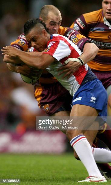 Wakefield's Paul White is tackled by Huddersfield's Andy Raleigh during the Engage Super League match at the Millennium Stadium Cardiff