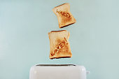 """Studio shot of toast popping out of a toaster with the words """"wakey wakey"""" on them against a turquoise background"""