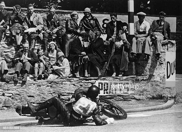 Wal Handley at the Junior TT Isle of Man 1933 Handley skids and comes off his Velocette as the crowd looks on He remounted his machine to finish...