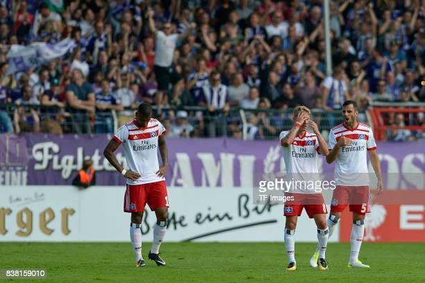 Walace of Hamburg and Lewis Holtby of Hamburg and Mergim Mavraj of Hamburg looks dejected during the DFB Cup match between VfL Osnabrueck and...