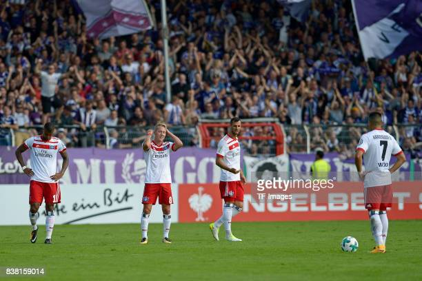 Walace of Hamburg and Lewis Holtby of Hamburg and Mergim Mavraj of Hamburg and Bobby Wood of Hamburg looks dejected during the DFB Cup match between...