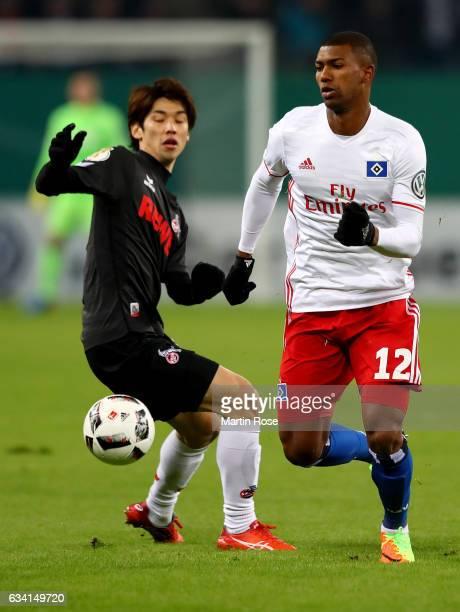 Walace of Hamburg and Yuya Osako of Koeln battle for the ball during the DFB Cup round of 16 match between Hamburger SV and 1 FC Koeln at...