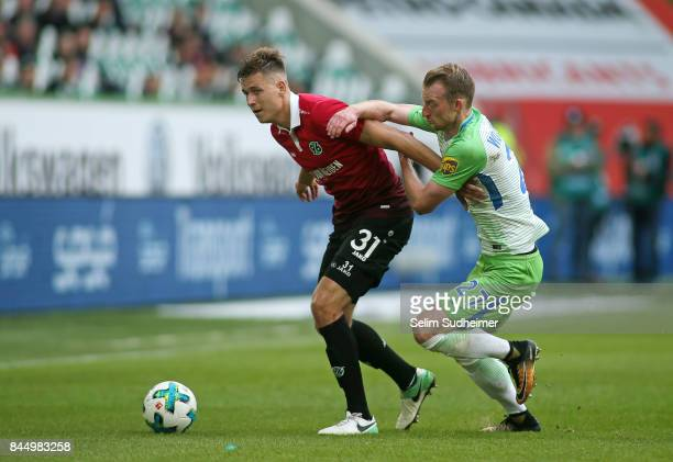 Waldemar Anton of Hannover 96 fights for the ball with Maximilian Arnold of VfL Wolfsburg during the Bundesliga match between VfL Wolfsburg and...