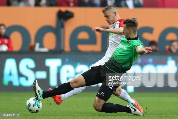 Waldemar Anton of Hannover fights for the ball with Jonathan Schmid of Augsburg during the Bundesliga match between FC Augsburg and Hannover 96 at...