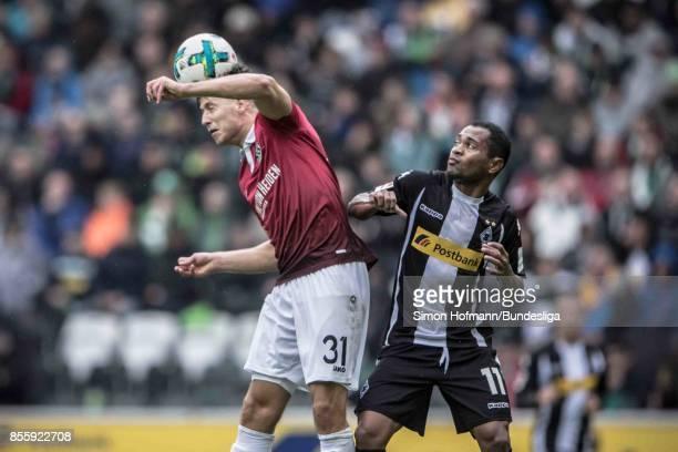 Waldemar Anton of Hannover jumps for a header with Raffael of Moenchengladbach during the Bundesliga match between Borussia Moenchengladbach and...