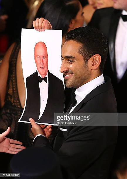 Waleed Aly holds a photo of Ray Meagher from Home and Away aloft as he arrives at the 58th Annual Logie Awards at Crown Palladium on May 8 2016 in...
