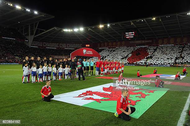 Wales and Serbia players line up for the national anthems while a red poppy is seen in the stand behind for Remembrance Day during the 2018 FIFA...
