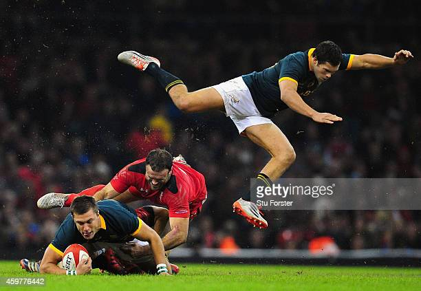 Wales centre Jamie Roberts tackles Handre Pollard as Jan Serfontein of South Africa goes flying during the Autumn international match between Wales...