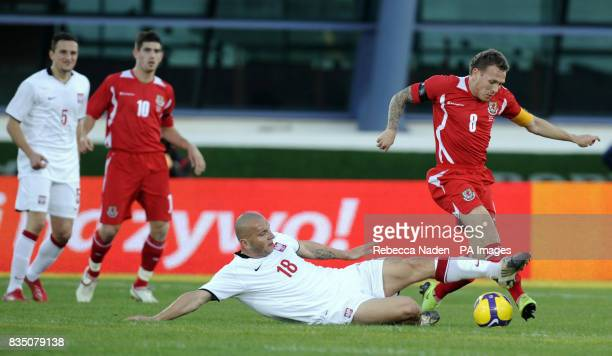 Wales' Craig Bellamy is tacked by Poland's Mariusz Lewandowski during the International Friendly at the Vila Real De Santo Antonio Sports Complex...
