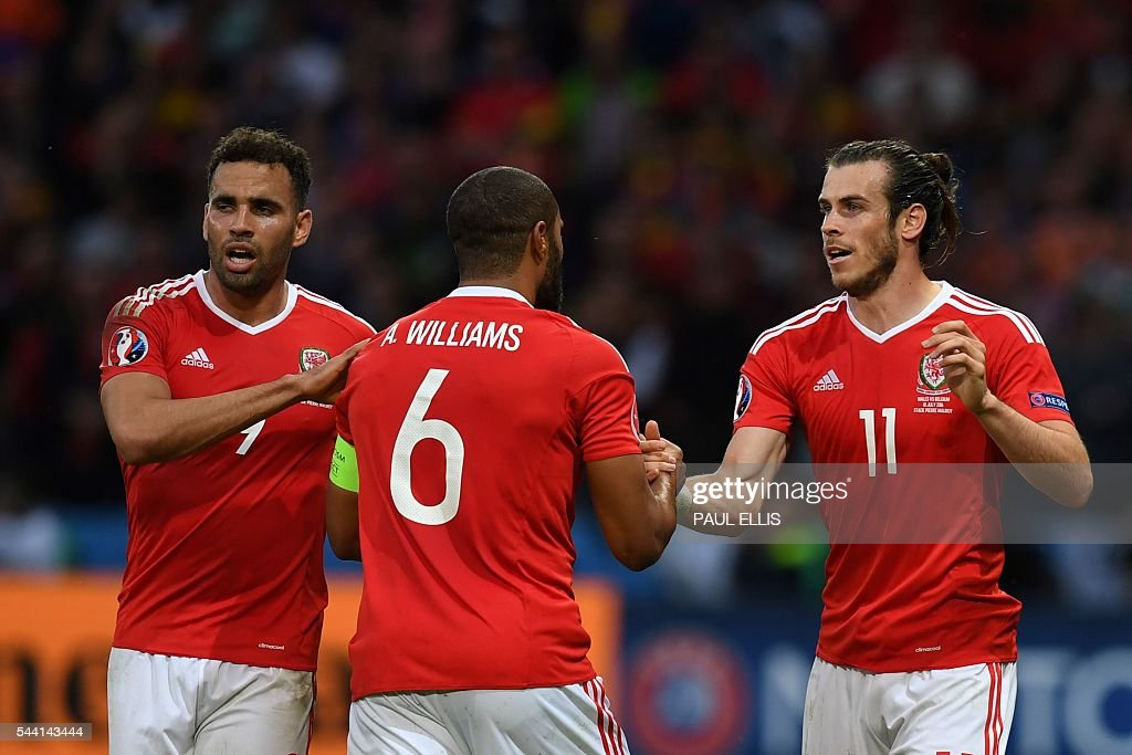 Wales' defender Ashley Williams (C) celebrates after scoring a goal with Wales' forward Hal Robson-Kanu and Wales' forward Gareth Bale during the Euro 2016 quarter-final football match between Wales and Belgium at the Pierre-Mauroy stadium in Villeneuve-d'Ascq near Lille, on July 1, 2016. / AFP / PAUL