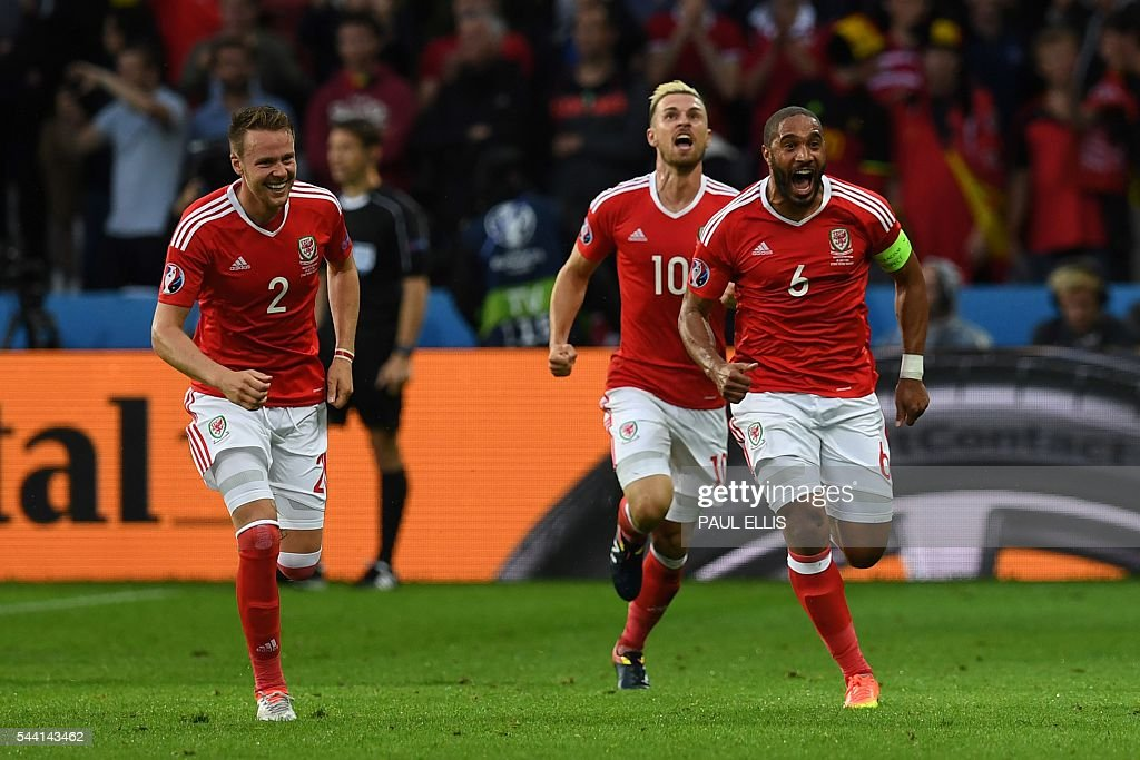 Wales' defender Ashley Williams (R) celebrates after scoring a goal with Wales' defender Chris Gunter and Wales' midfielder Aaron Ramsey during the Euro 2016 quarter-final football match between Wales and Belgium at the Pierre-Mauroy stadium in Villeneuve-d'Ascq near Lille, on July 1, 2016. / AFP / PAUL