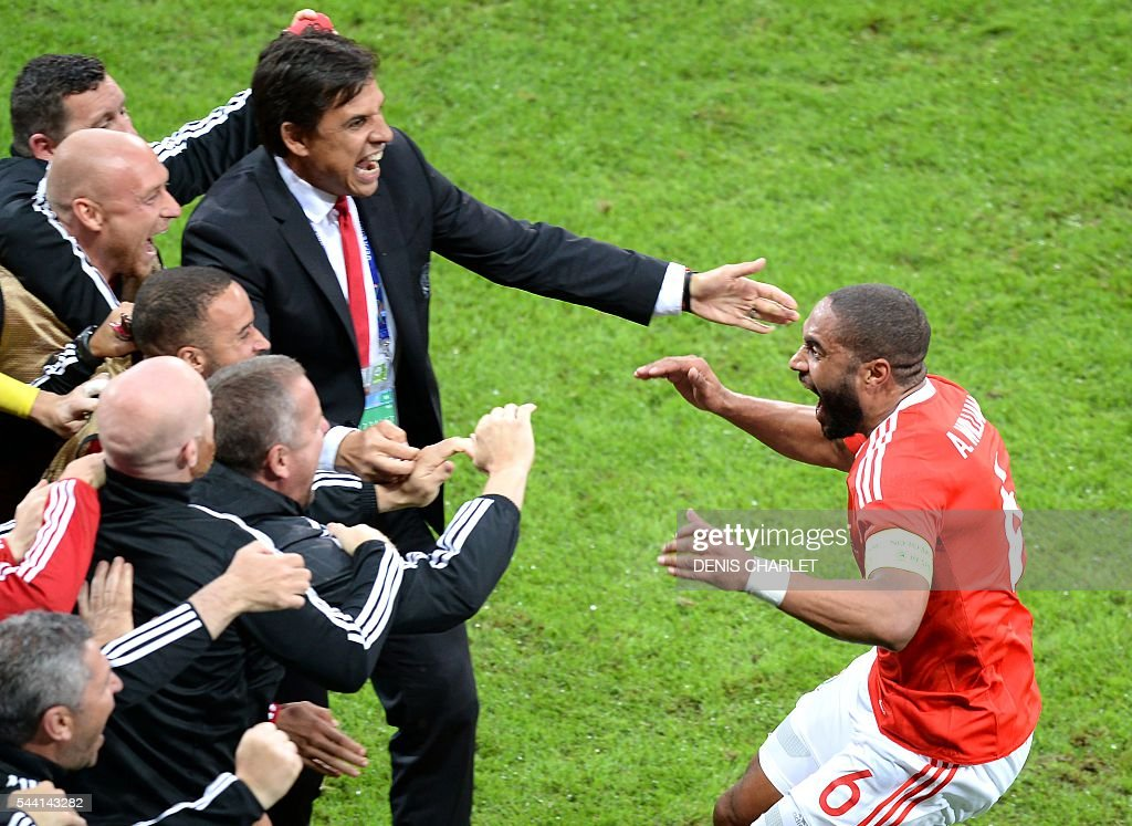 Wales' defender Ashley Williams (R) celebrates with Wales' coach Chris Coleman (C) and teammates after scoring a goal during the Euro 2016 quarter-final football match between Wales and Belgium at the Pierre-Mauroy stadium in Villeneuve-d'Ascq near Lille, on July 1, 2016. / AFP / Denis Charlet