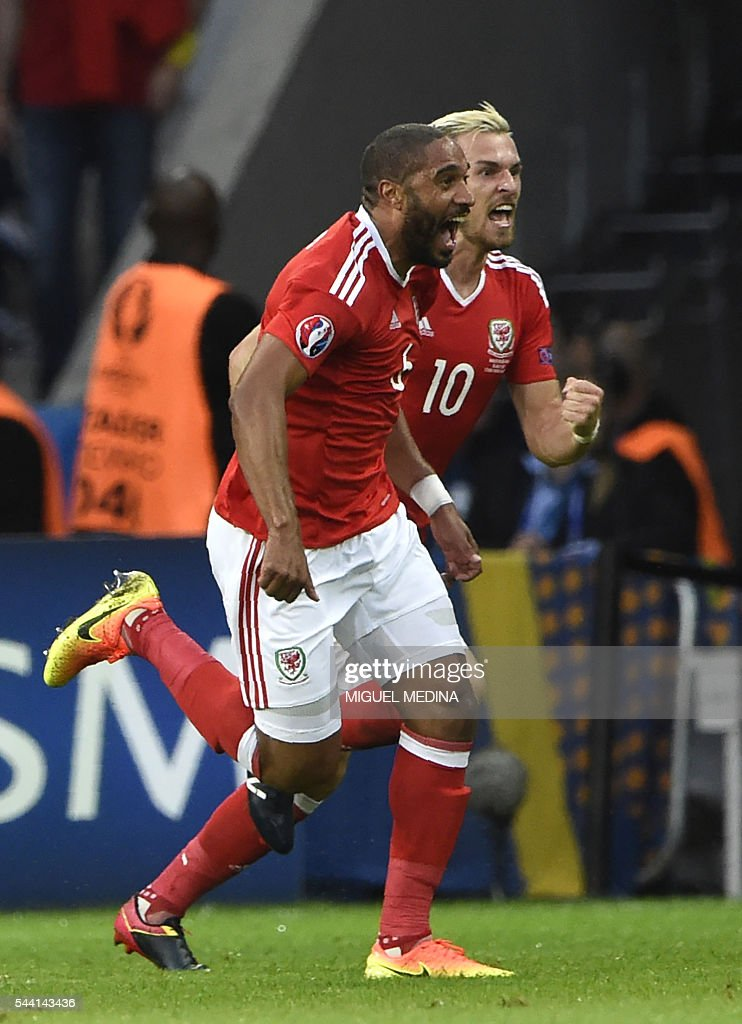 Wales' defender Ashley Williams celebrates with Wales' midfielder Aaron Ramsey (back) after scoring a goal during the Euro 2016 quarter-final football match between Wales and Belgium at the Pierre-Mauroy stadium in Villeneuve-d'Ascq near Lille, on July 1, 2016. / AFP / MIGUEL