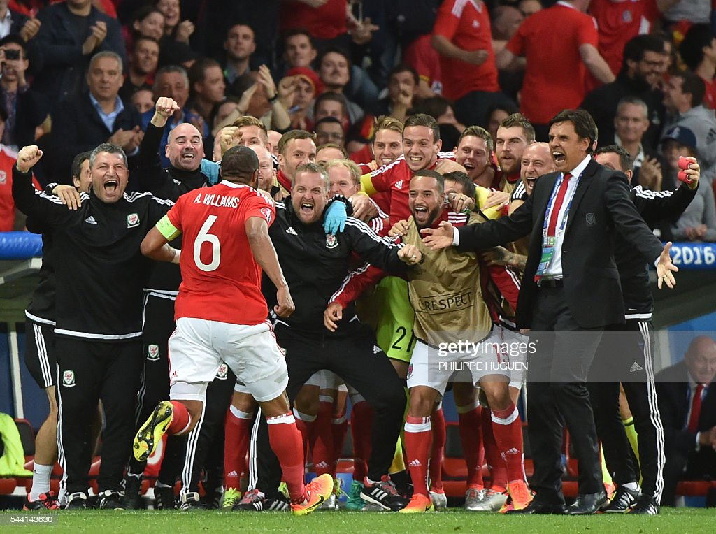 Wales' defender Ashley Williams (C) runs towards Wales' coach Chris Coleman (R) and teammates as he celebrates after scoring a goal during the Euro 2016 quarter-final football match between Wales and Belgium at the Pierre-Mauroy stadium in Villeneuve-d'Ascq near Lille, on July 1, 2016. / AFP / PHILIPPE