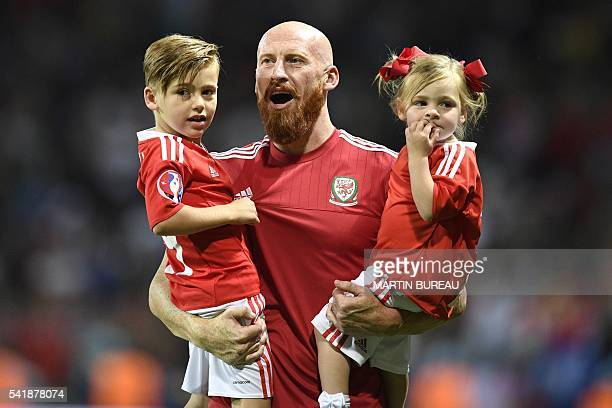 Wales' defender James Collins holds his children as he celebrates the team's 30 win in the Euro 2016 group B football match between Russia and Wales...