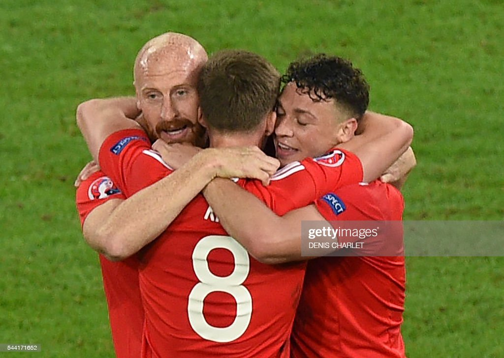 Wales' defender James Collins, Wales' midfielder Andy King and Wales' defender James Chester celebrate at the end of the Euro 2016 quarter-final football match between Wales and Belgium at the Pierre-Mauroy stadium in Villeneuve-d'Ascq near Lille, on July 1, 2016. / AFP / DENIS