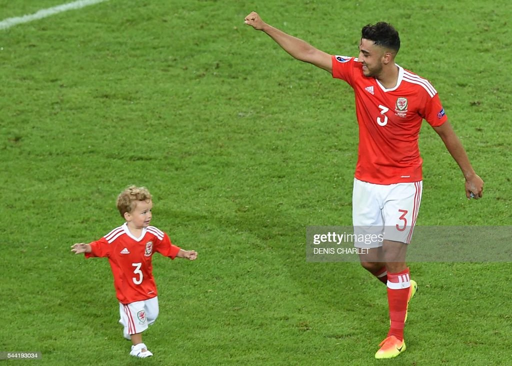 Wales' defender Neil Taylor celebrates with his son Marley at the end of the Euro 2016 quarter-final football match between Wales and Belgium at the Pierre-Mauroy stadium in Villeneuve-d'Ascq near Lille, on July 1, 2016. / AFP / DENIS