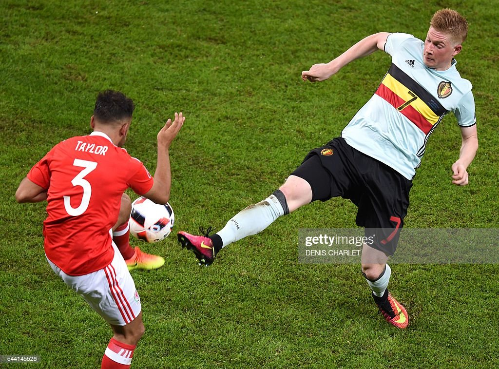 Wales' defender Neil Taylor (L) challenges Belgium's midfielder Kevin De Bruyne during the Euro 2016 quarter-final football match between Wales and Belgium at the Pierre-Mauroy stadium in Villeneuve-d'Ascq near Lille, on July 1, 2016. / AFP / DENIS