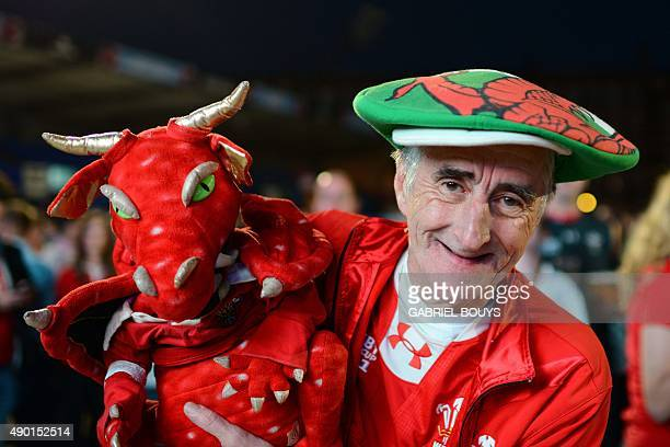 A Wales fan is pictured as he watches the England v Wales rugby union game on a giant television screen at a fanzone in Cardiff Wales on September 26...