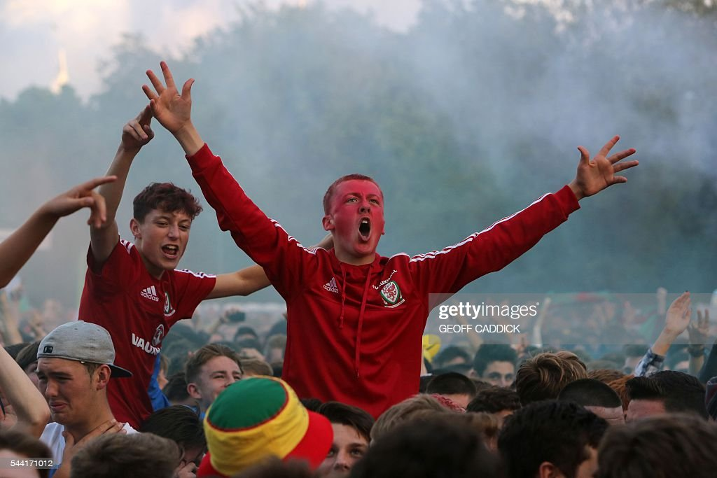 Wales fans celebrate after Wales score their second goal to take the lead at a screening of the Euro 2016 quarter final match between Wales and Belgium at the fan zone in Cardiff, south Wales on July 1, 2016. / AFP / Geoff CADDICK