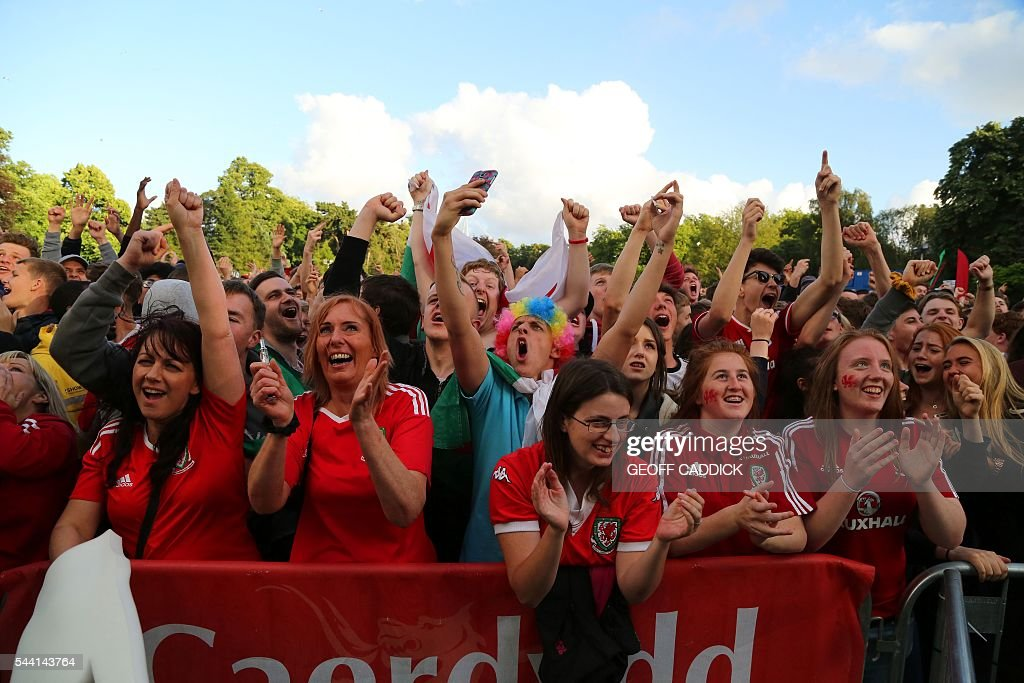 Wales fans celebrate as their team equalize at a the screening of the Euro 2016 quarter final match between Wales and Belgium at the fan zone in Cardiff, south Wales on July 1, 2016. / AFP / Geoff CADDICK